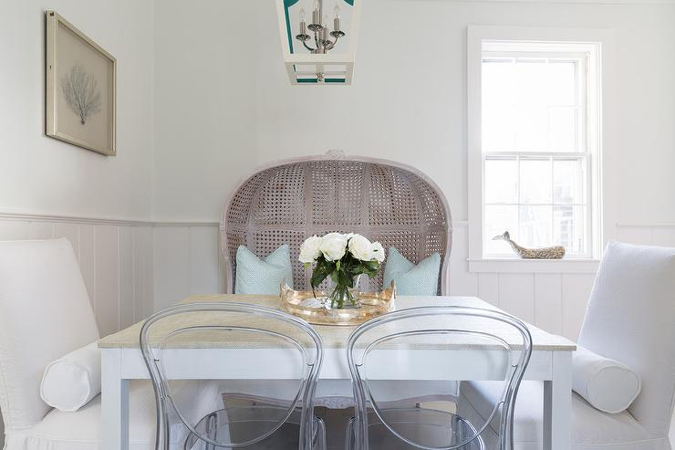 white and turquoise blue pagoda lantern hangs over a white dining table lined with gray wash dome dining settee white slipper dining chairs and acrylic