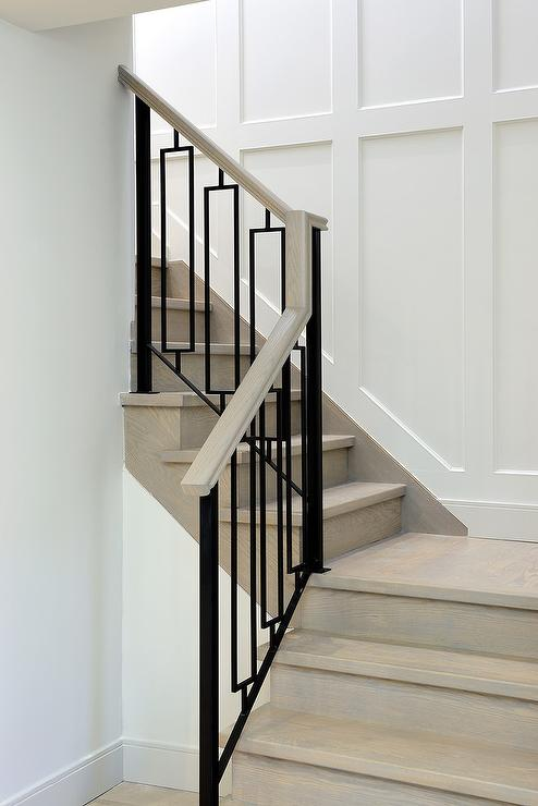 A Gray Wash Wood Staircase Is Finished With Hollow Iron Balusters Alongside  A Staircase Wall Clad In Wainscoting.