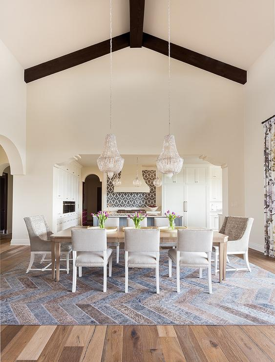 gorgeous dining room with a long wood table is surrounded by light gray leather and velvet dining chairs under two light gray beaded chandeliers