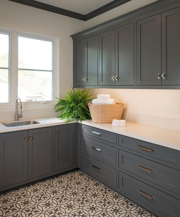 charcoal gray laundry room boasts charcoal gray shaker cabinets adorned with polished nickel latches and pulls paired with offwhite quartz countertops and