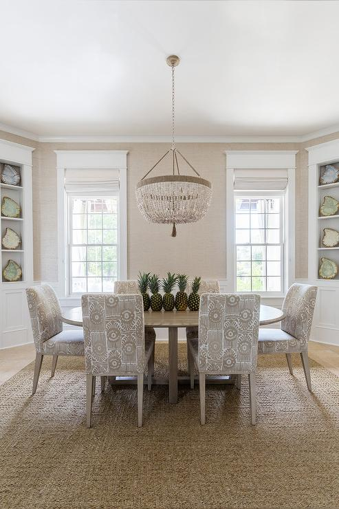 Ro Sham Beaux Malibu Chandelier Illuminates An Oval Beige Dining Table  Lined With Beige Print Dining Chairs Placed Atop A Jute Rug.