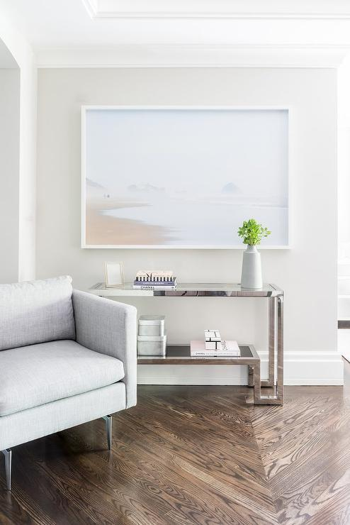 A Modern Gray Linen Chair Stands Before A White Gallery Framed Beach Print  Stands Over A Glass And Chrome Greek Key Console Table Placed Atop A Wood  ...