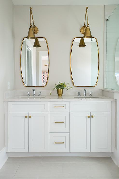 Two Antique Brass Swing Arm Pendants Illuminate Mirrors Placed Over A White Dual Washstand Adorned With Hardware Topped Quartz