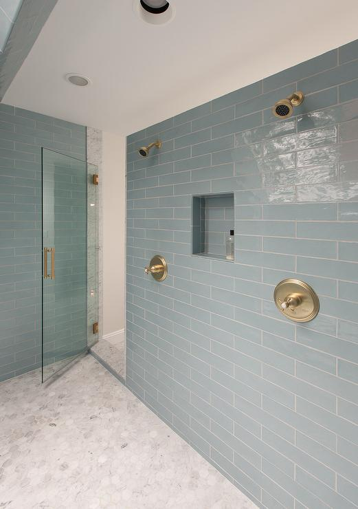 Amazing master bathroom features a glass shower door with brass handle  which opens to a large shower clad in linear blue glass tiles lined with  his and her ...