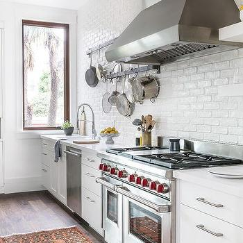 white painted exposed brick kitchen wall