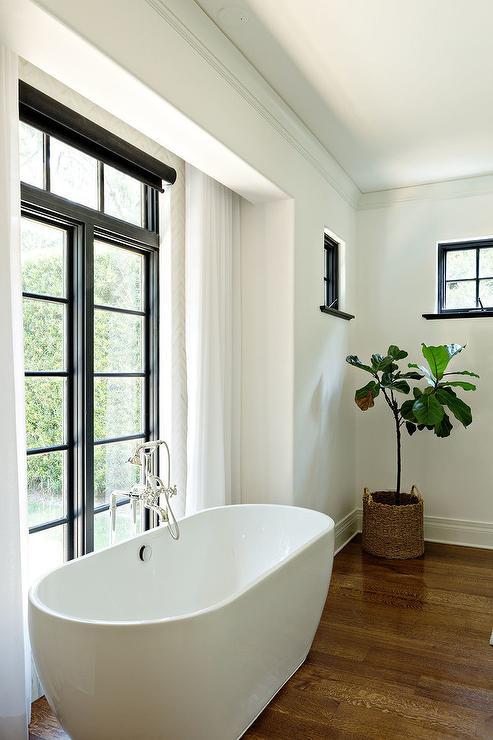 Modern Freestanding Bathtub In Front Of Black Framed Doors