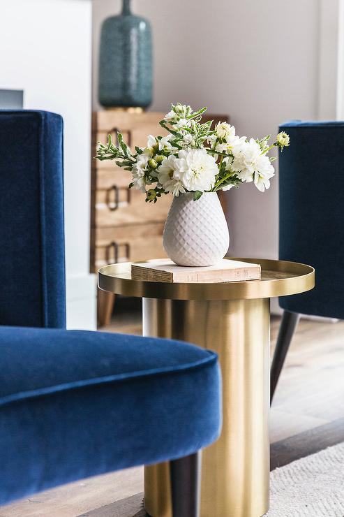 Luxurious Royal Blue Chair In Velvet Upholstery Is Paired With A Brass Cylindrical Accent Table Displaying White Textured Ceramic Vase Flowers