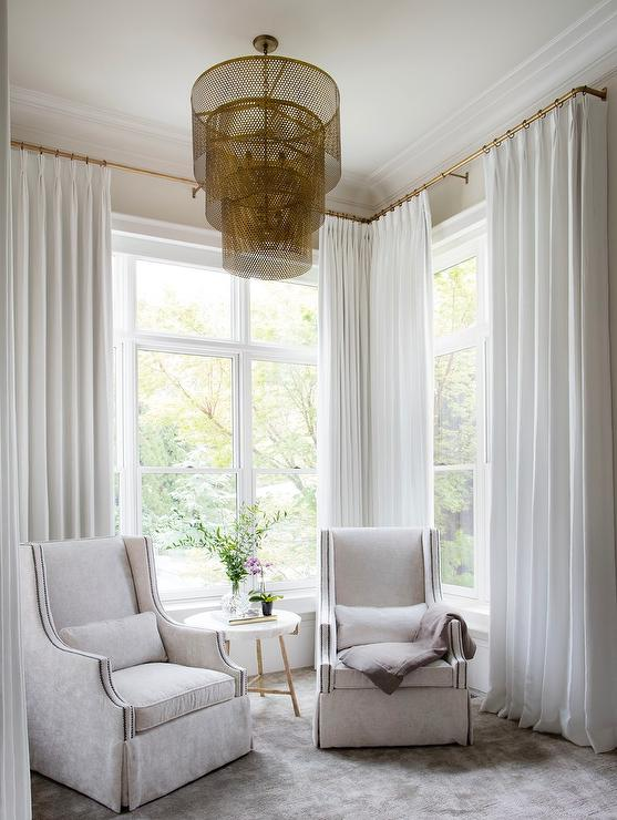 welcoming bedroom sitting area featuring two light gray velvet wingback chairs placed on a gray rug on either side of a marble and brass accent table