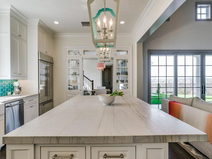 A White Kitchen Island Topped With A White Macaubas Quartzite Countertop Is Lit By Two Gray And Teal Lanterns Complementing Teal Hive Backsplash Tiles