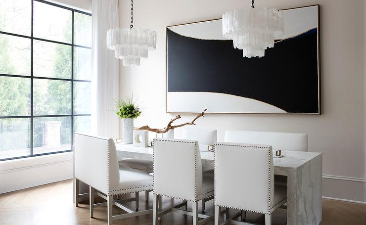 Sleek Modern Black And White Dining Room Boasts Two Tiered Capiz Chandeliers Hung Over A Marble Waterfall Table Seating Leather