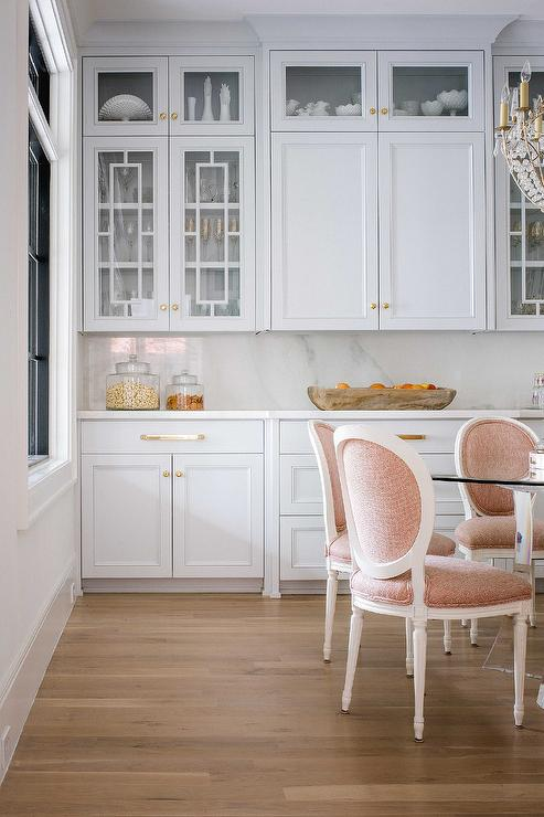 Light Gray Butler Pantry Features Pink Round Back French Dining Chairs Positioned Around A Lucite Table Lit By Crystal Beaded Chandelier
