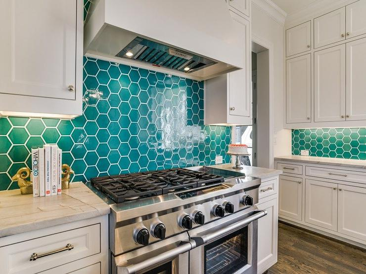 A white vent hood is mounted against teal hive backsplash tiles between  stacked white shaker cabinets adorned with polished nickel knobs. - Teal Hive Kitchen Backsplash Tiles Design Ideas