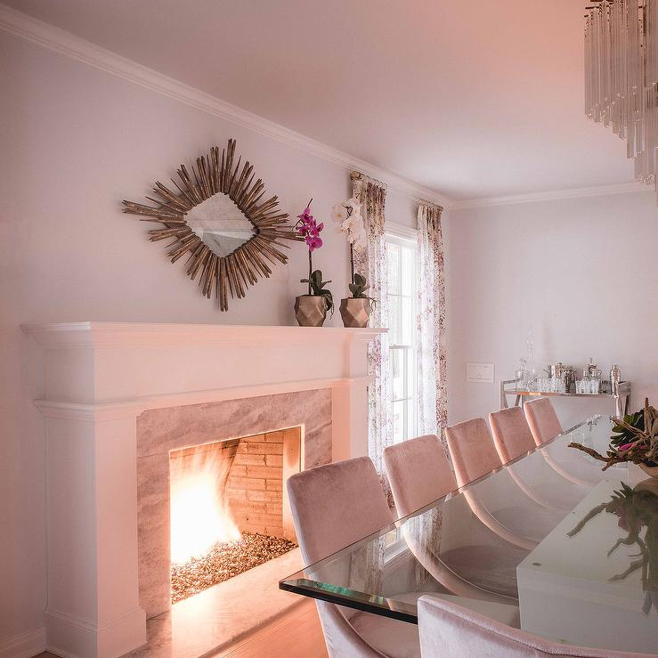 A Gold Leaf Diamond Mirror Features Sunburst Frame Hanging Over White Marble Fireplace In An Art Deco Dining Room