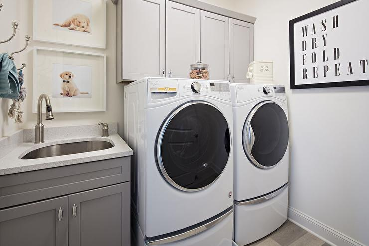 Gray Laundry Room Cabinets With White Front Load Washer And