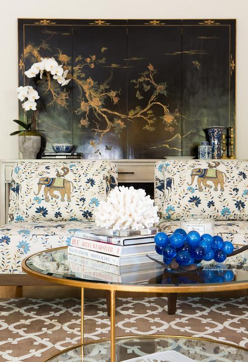 Stunning Eclectic Living Room Features A Round Brass And Glass Tiered Coffee Table Placed On Brown Moroccan Trellis Rug In Front Of Two Elephant Print