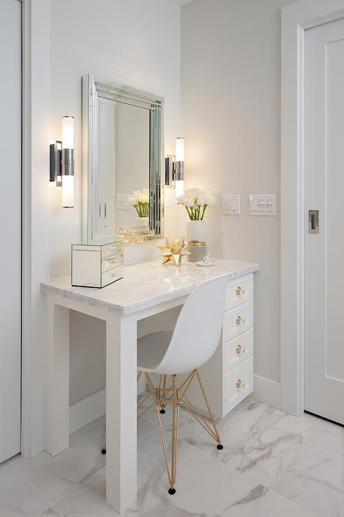 white and gold vanity table. White master bathroom is completed with an Eames Molded Plastic Chair  placed on marble porcelain floor tiles in front of a white dressing table accented and Gold Hollywood Regency Dressing Table