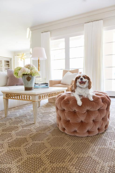 A Round Pink Velvet Tufted Ottoman Sits On A Honeycomb Rug In Front Of A  French Gray And Gold Coffee Table Seating A White Sofa Topped With A  Lavender ...