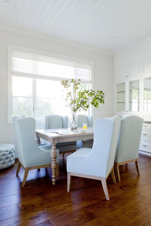 under a white beadboard ceiling a gray dining table with turned legs is surrounded by sky blue wingback dining chairs placed in front of a window covered