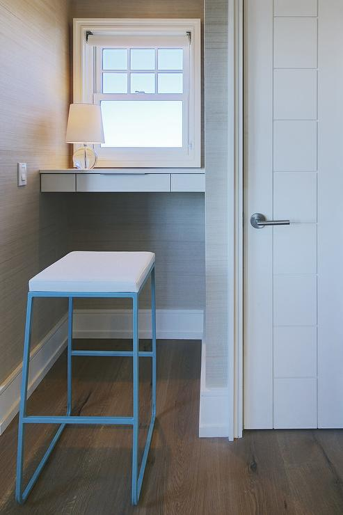 A Sleek Blue Metal Desk Stool Sits In Front Of White Floating Mounted Nook Covered Gray Grasscloth Wallpaper Framing Window Lit By Terri