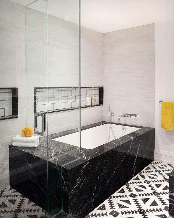 Black Marble Clad Bathtub With Cement Floor Tiles