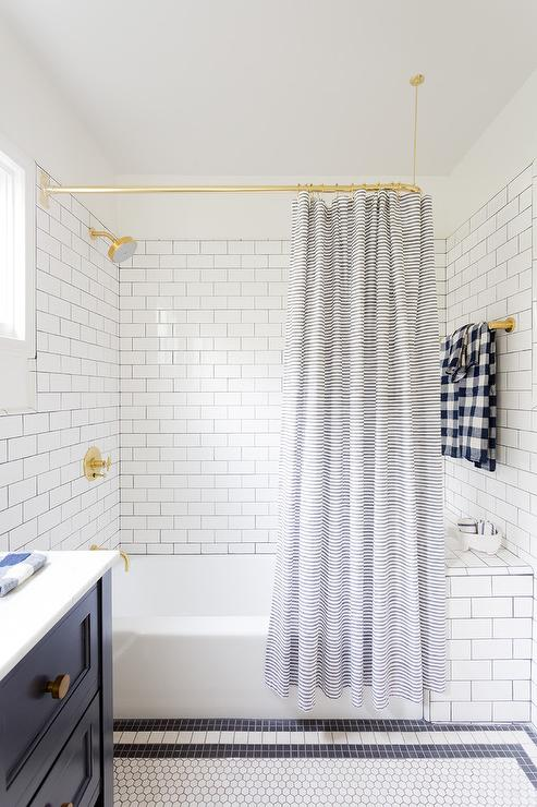 Beautifully Designed White And Blue Boys Bathroom Is Fitted With A Polished Brass Curved Shower Rail Holding Striped Curtain In Front Of