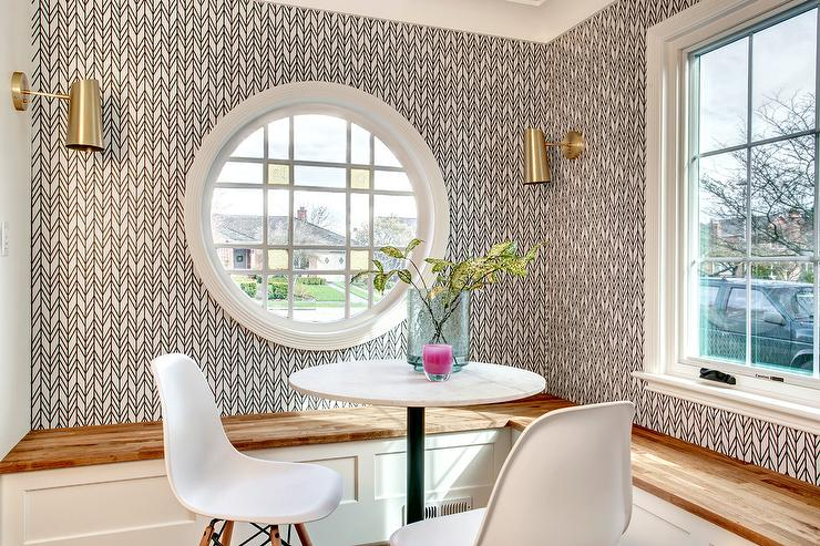 Framed By Black And White Wallpaper, A Round Window Is Illuminated By Brass  Sconces And Positioned Above A White L Shaped Contrasted With A Wood Seat.