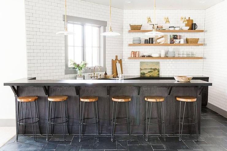 Six Crate Barrel Origin Backless Bar Stools Sit Beneath A Black Quartz Countertop Accenting Dark Brown L Shaped Oak Island Illuminated By Three White