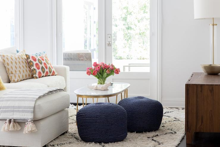 Two Navy Blue Knitted Poufs Sit On A Beni Ourain Rug Beside An Oval Marble  And Brass Cocktail Table Placed In Front Of An Ivory Sofa With A Chaise  Lounge ...