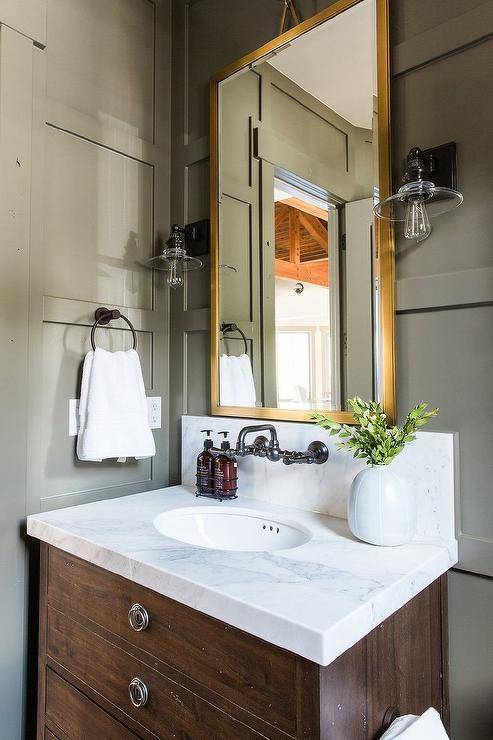 a gold vanity mirror flanked by vintage barn sconces is mounted on a gray wainscot wall above a restoration hardware maison single vanity