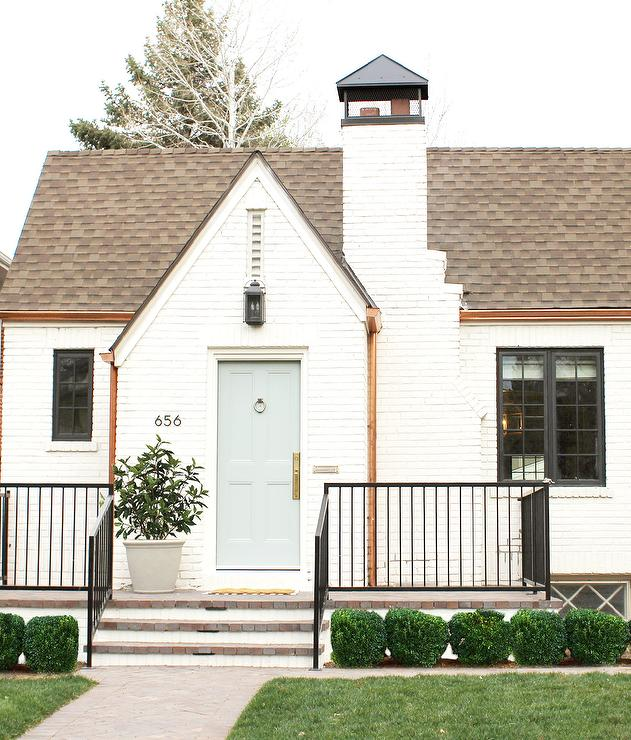 A White Brick Tudor Style Home Accented With A Pale Blue Gray Front Door  And Brown Roof Shingles Is Finished With Modern House Numbers And An Iron  Staircase ...