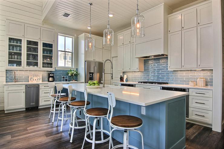 Five White Metal Industrial Bar Stools Sit In Front Of A Blue Center Island Finished With Quartz Countertop Fitted Sink Stainless