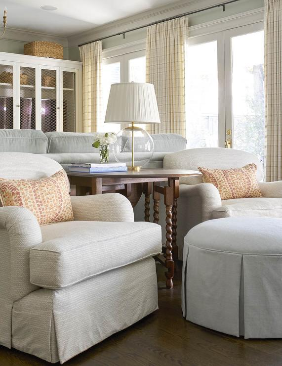... Accent Table And Illuminates Two White Patterned Roll Arm Chairs Topped  With Orange And Pink Pillows And Paired With A Round White Skirted Ottoman.