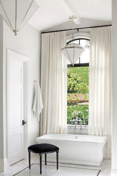 White curtains behind waterworks empire freestanding Empire bathrooms