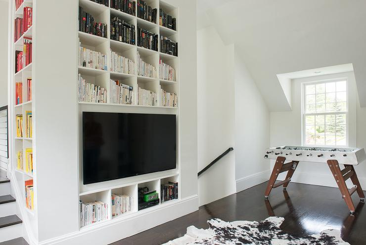 ceiling built in book cubbies are fitted with a large flat panel television fixed facing a black and white cowhide rug placed beside a foosball table