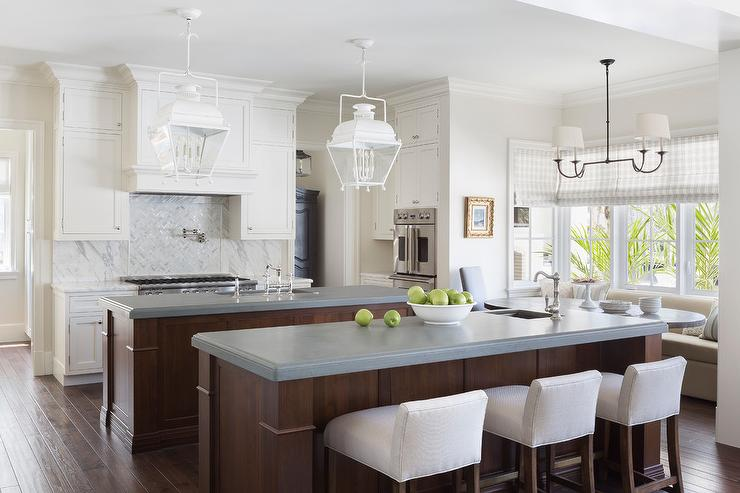 Well appointed eat-in kitchen is lit by white carriage lanterns hung over 2 sets of wood islands topped with gray countertops. & White Low Back Upholstered Counter Stools Design Ideas islam-shia.org