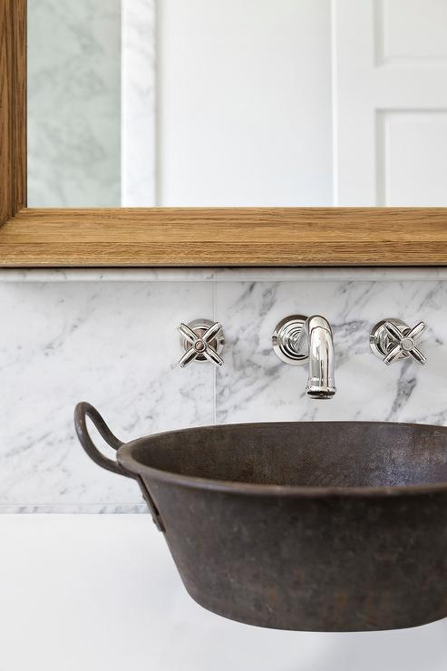 a galvanized metal sink sits on a white quartz countertop beneath a vintage style faucet mounted to a marble tiled backsplash beneath an oak beveled vanity