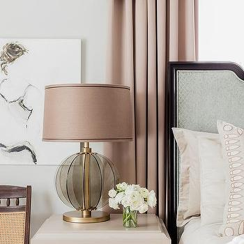 pink curtains behind gray headboard