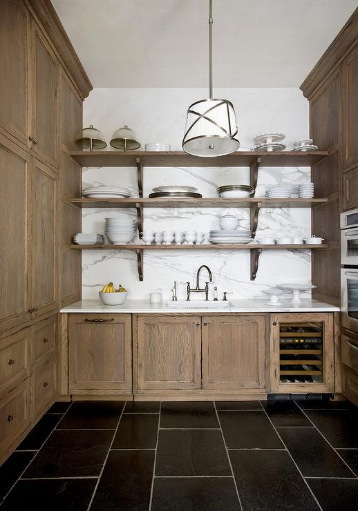 Stained Oak Pantry Cabinets With Marble Slab Backsplash
