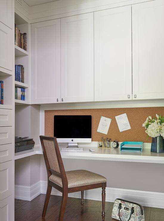 A Square Back Desk Chair Sits At White Floating L Shaped Mounted To Gray Wall Beneath Cork Board Fixed Under Cabinets Accented With Nickel