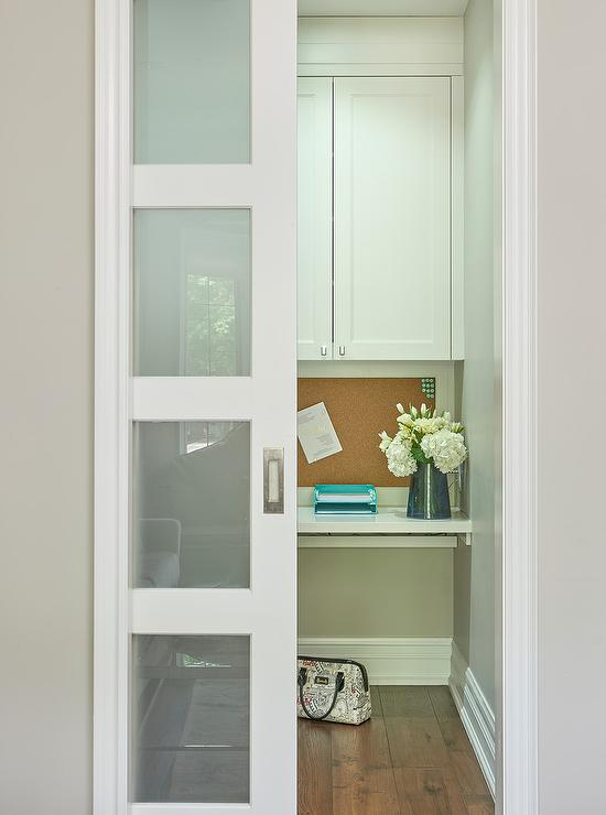 a frosted glass pocket door opens to a small home office featuring a white floating desk positioned against a gray wall and beneath a cork board mounted