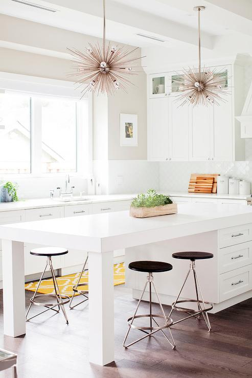 Two Silver Sputnik Chandelier Lights Hang Above A Long White Island Finished With Legs And Seating Arteriors Wyndham Counter Stools Beneath Marble