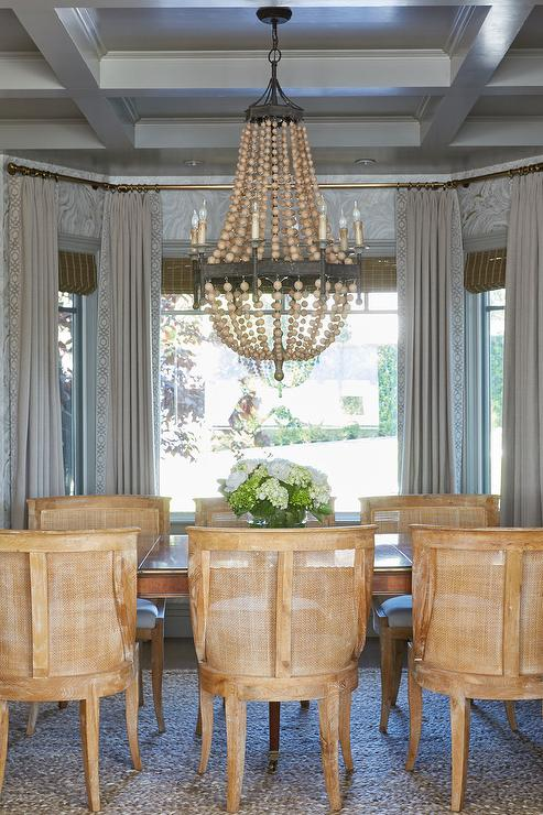 Chandelier Hangs From A Gray Coffered Ceiling Above An Antique Dining Table Surrounded By Wood And Mesh Chairs Positioned In Front Of Bay Windows