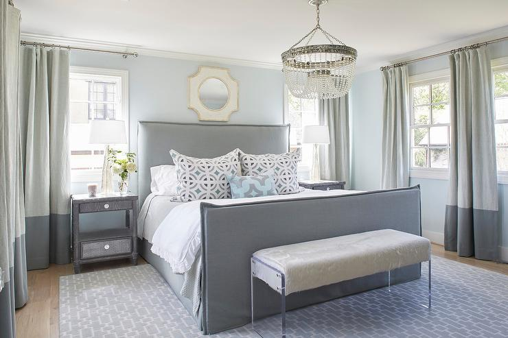 Well Designed Gray Bedroom Is Furnished With A Gray Upholstered Bed Dressed In White And Gray Bedding Topped With Gray And Blue Pillows Lit By A Beaded