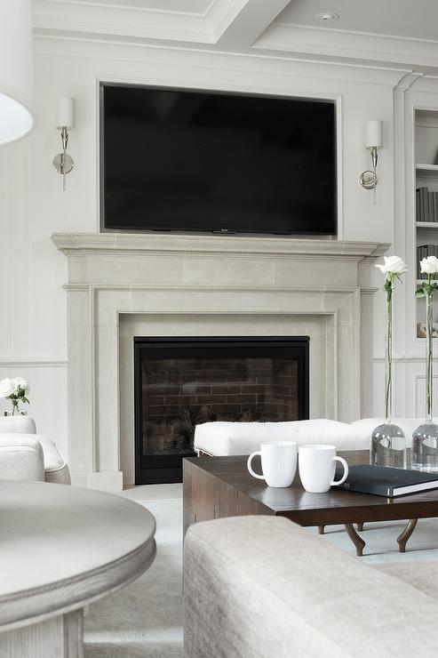 Light gray limestone fireplace with mantel showcasing a tv niche flanked by long polished nickel sconces.