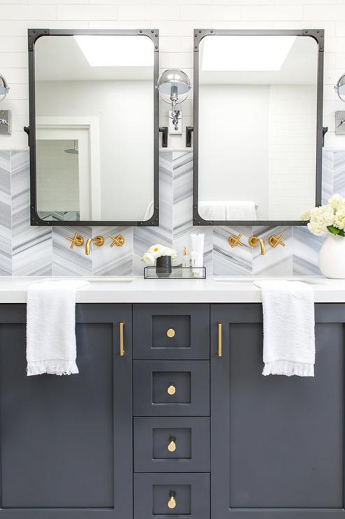 Restoration Hardware Hemisphere Sconces Are Mounted To White Linear Wall Tiles Flanking Industrial Rivet Flat Mirrors Hung Above A