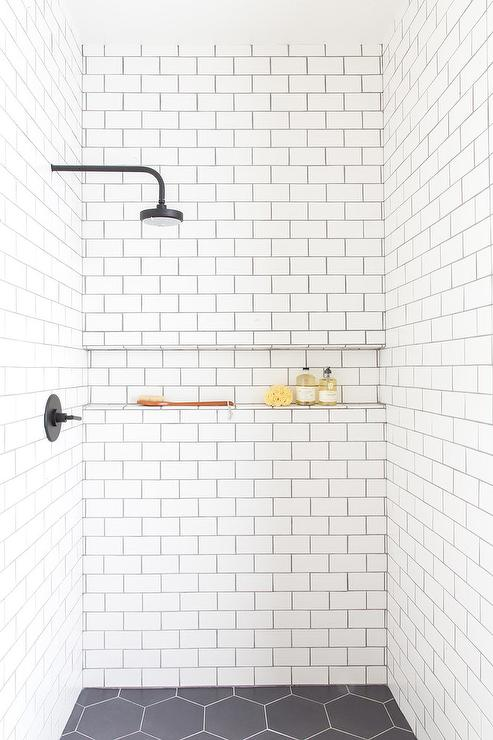 An Oil Rubbed Bronze Shower Head Is Fixed To White Subway Shower Surround  Tiles Accented With Black Grout And Finished With A Tiled Ledge Positioned  Over ...
