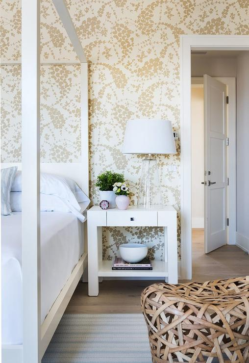 Clad in China Seas Lysette Wallpaper, this elegant bedroom boasts a white canopy bed placed on a white and blue rug, dressed in white hotel bedding, ...