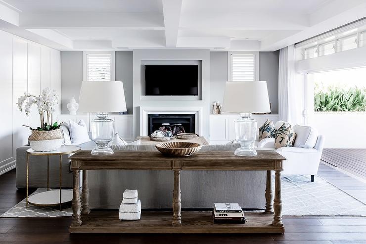 Wood Barade Console Table Behind A Gray Sofa In Classic White And Transitional Living Room