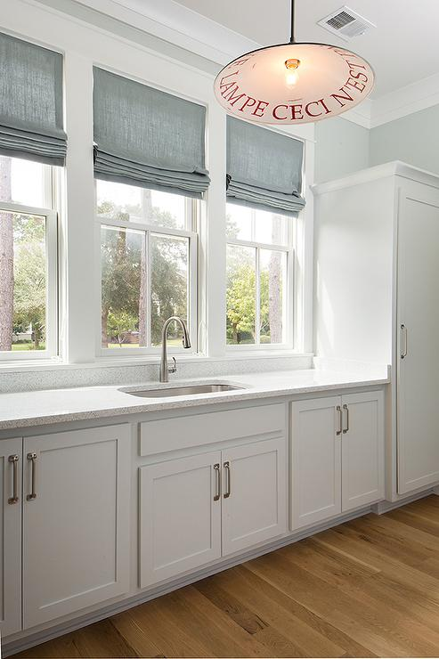 Eye Catching White Cottage Style Laundry Room With Light Gray Shaker  Cabinets, Nickel Pulls And Corian Countertops.