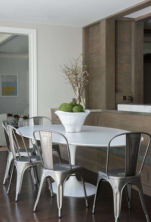 tolix chairs surround a saarinen oval dining table that also seats a walnut stained builtin dining bench topped with a charcoal gray cushion
